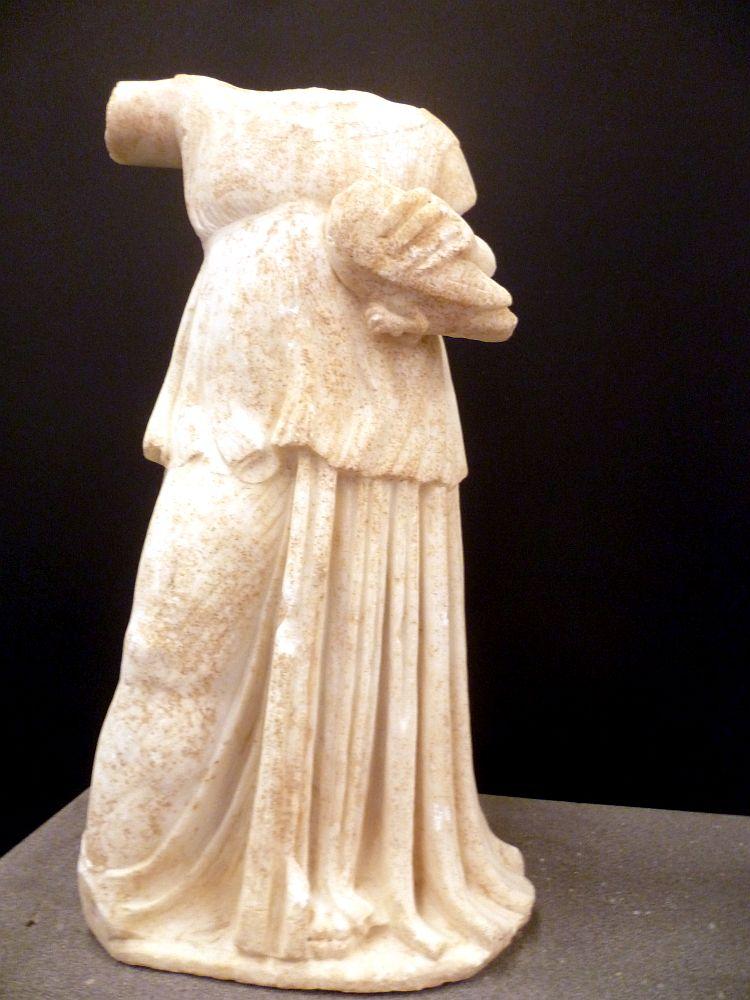 Eine Marmorskulptur aus der Antike. Kopf und Arme sind abgebrochen. Die Figur eines Kindes in Mädchenkleidung ist so zerbrochen, dass noch eine Hand die einen Vogel hält zu sehen ist.