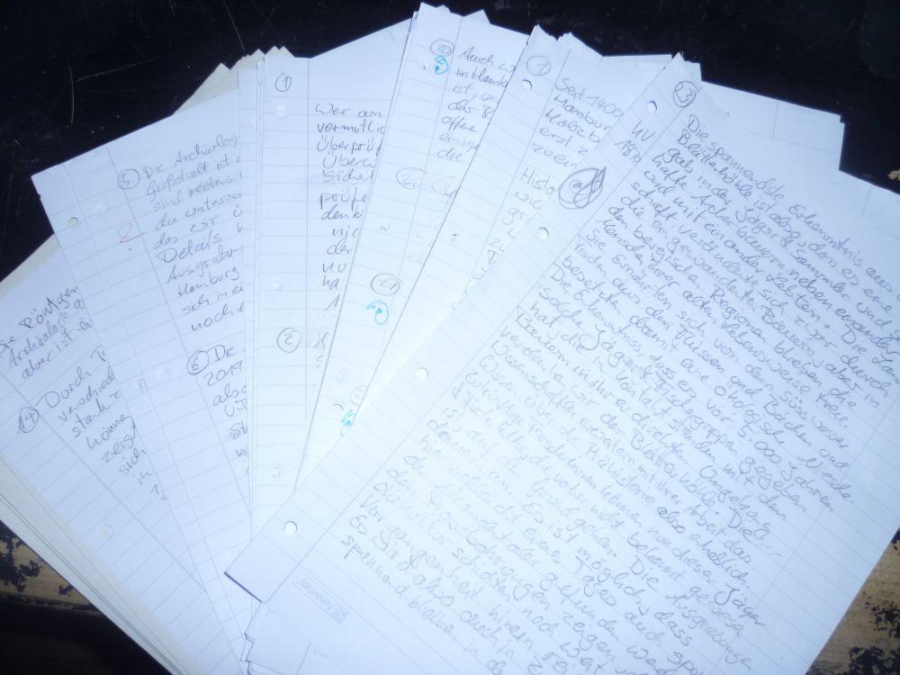 Voll geschriebene Zettel, die aufgefächert auf einer schwarzen Tischplatte liegen