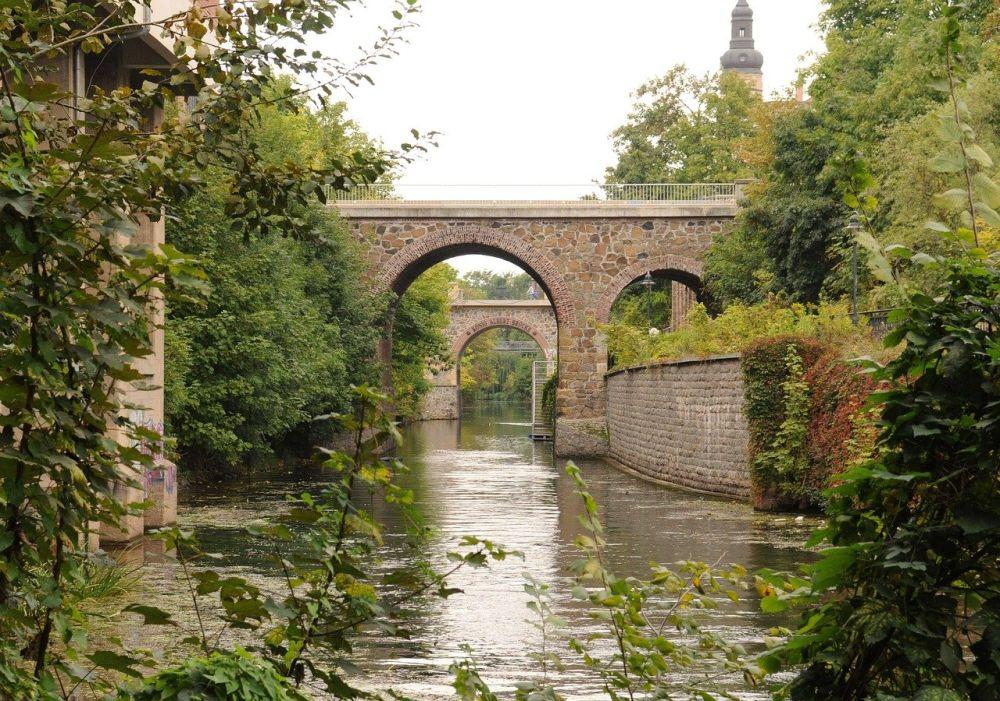 Brücke aus Stein über dem Plagwitzer Kanal in Leipzig. Die Brücke besteht aus Grob behauenen Stein und ist in einem hohen Bogen über dem Waserlauf geführt. Im Hintergrund ist eine zweite Brücke gleicher Bauart zu erkennen. Das Panaorama ist von grünen Büschen und Bäumen gerahmt.