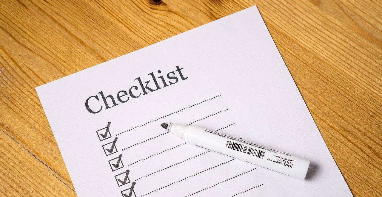 Zettel auf einem Holztisch. Auf dem Zettel steht das Wort Checklist geschrieben, darunter ist eine leere Liste. Ein Stift ist bereit gelegt.