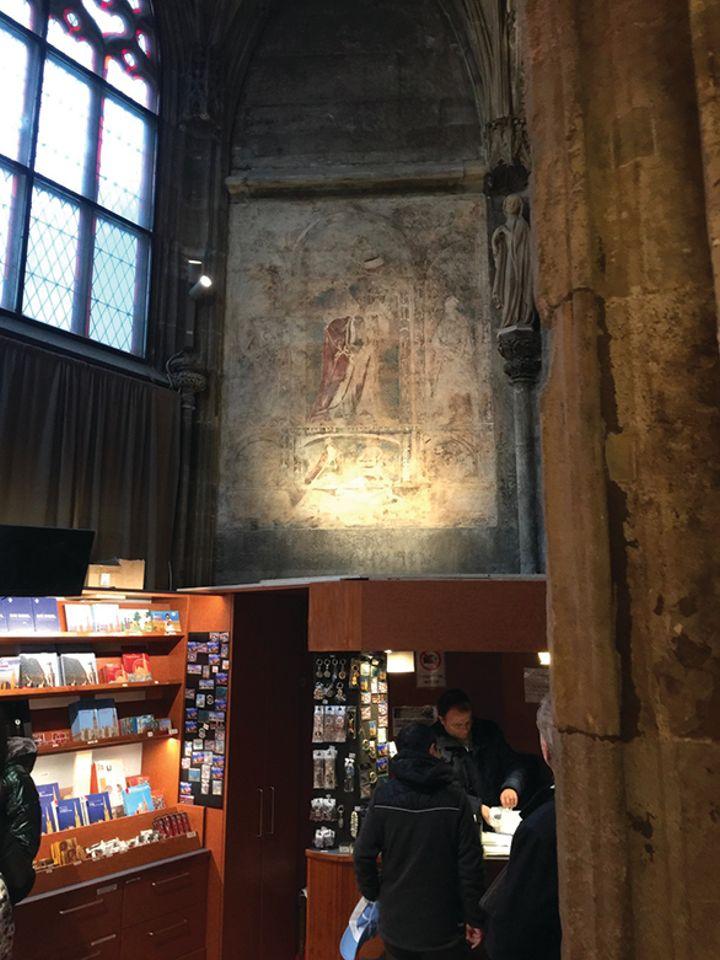 Innenaufahme aus dem Stephansdom. An der Wand befindet sich ein sehr verblasstes bild, das von einer Lampe angestrahlt wird. es ist oberhalb eines Kassenhäuschens angebracht, in dem sich ein Geschenkshop befindet.