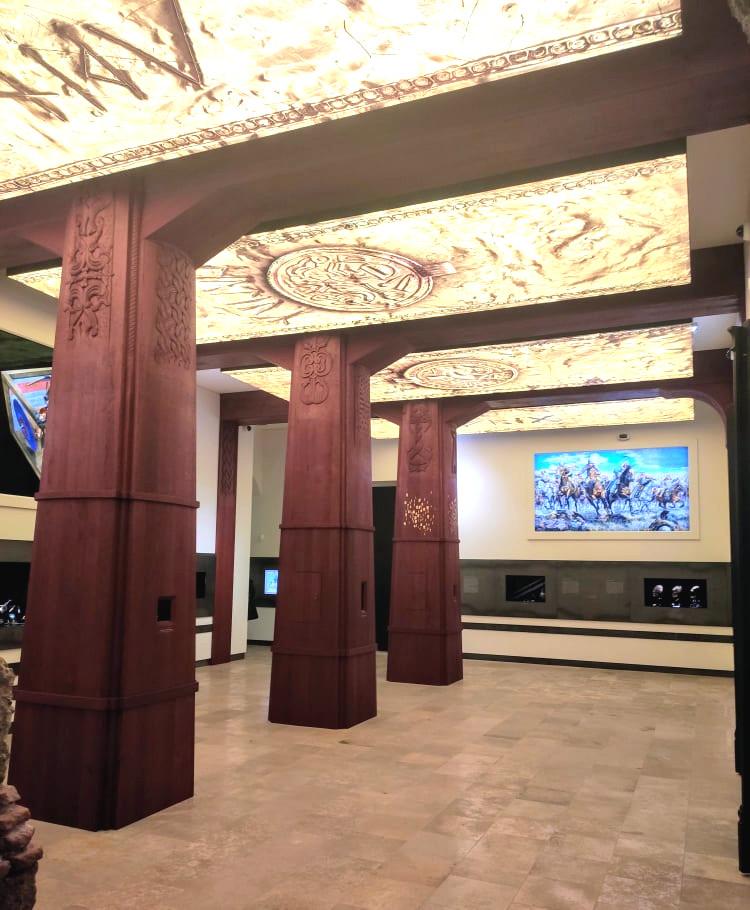 Eine Halle die mit indierekten Licht beleuchtet ist. Die Halle hat Drei rote Säulen.