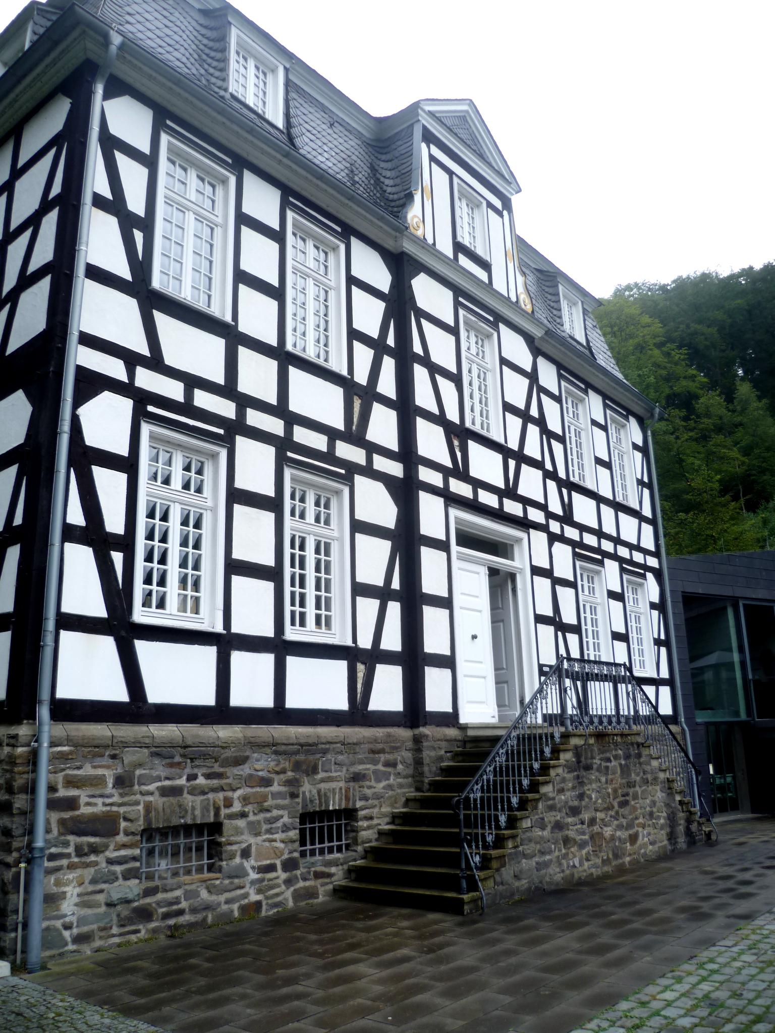 Ein großes Barock Fachwerkhaus, mit einem mit dunklen Schindeln gedeckten Dach. Das Haus ist weiß mit schwarzen Balken. Das Fundament besteht aus Stein, und man gelangt über eine Steintreppe in die erste Etage. Das Gebäude ist sehr stattlich.