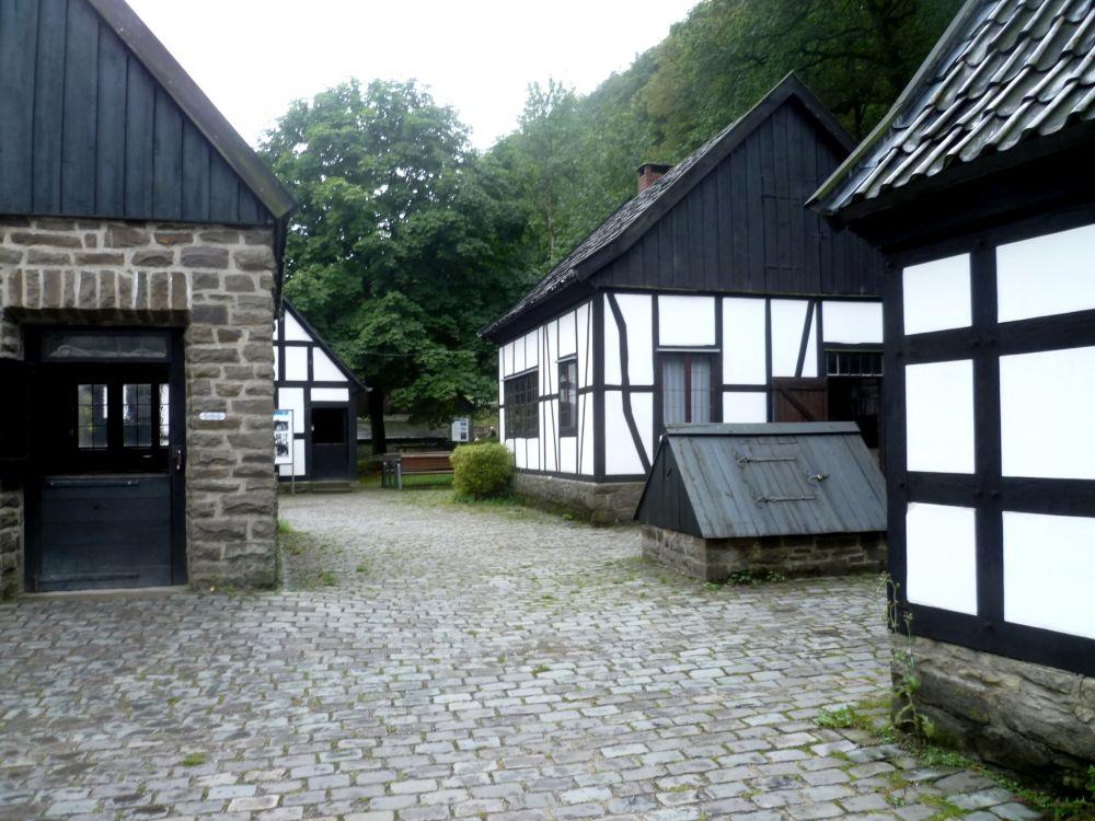 Vier alte Gebäude und ein Schuppen umgeben eine Gepflasterte Strasse. Es handelt sich um eingeschossiege Gebäude, die meistens nur einen Raum haben. Drei der Häuser Sind in weise Fachwerkbauten mit schwarzen Balken, dass vierte ist aus Stein gebaut.
