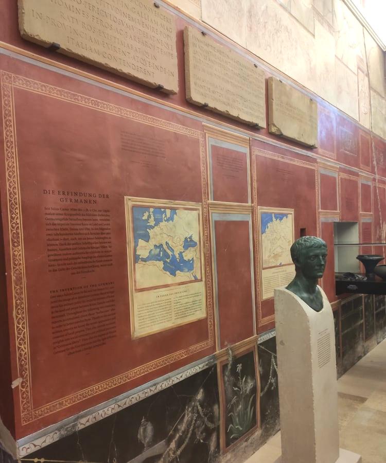 Eine rote Wand mit vielen Karten, Beschriftung, und Inschriftsteinen. Eine Büste aus Bronze von Tacitus ist vor dieser Wand aufgestellt.