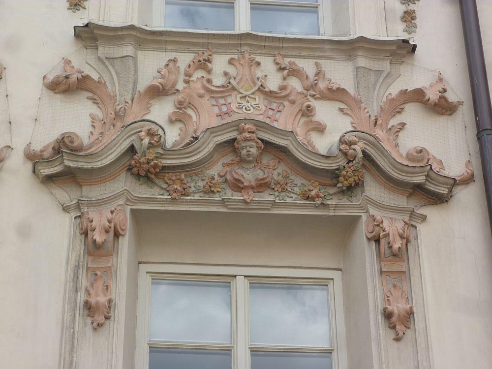 Rosa Stuck über einem Fenster. In Rosa Bemalte Blätter und Blume, ein Weise geschwungener Bogengiebel, und ein Puttenkopf sind über dem Fenster zu sehen.