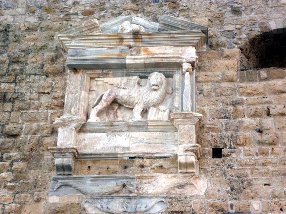 Eine Mauer mit einem Eingesetzten und gerahmten Relief aus Marmor. Das Reief zeigt einen geflügelten Löwen.