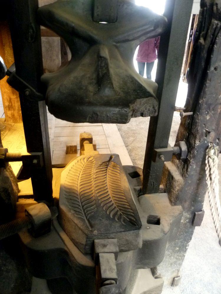 Ein großer Hammer hängt über einer Matritze die zwei Farnblätter zeigt.
