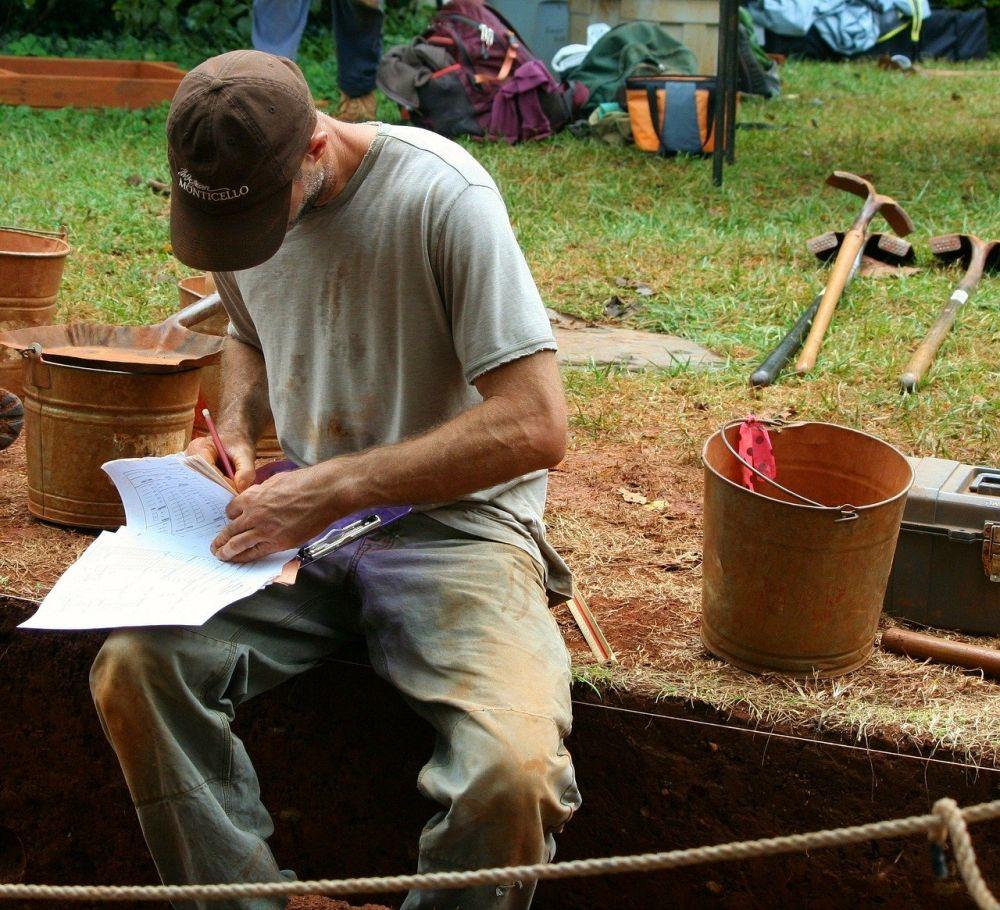 Ein Mann sitzt auf einer Profilkante bei einer Ausgrabung. Seine Klamotten sind dreckig, und er ist damit beschäftigt Zettel auszüllen. Diese liegen auf seinem Schoss. Das Gesicht des Mannes ist hinter einer Schirmmütze verborgen. Um ihn herum stehen einige Eimer und im Hintergrund liege ein paar Schaufeln