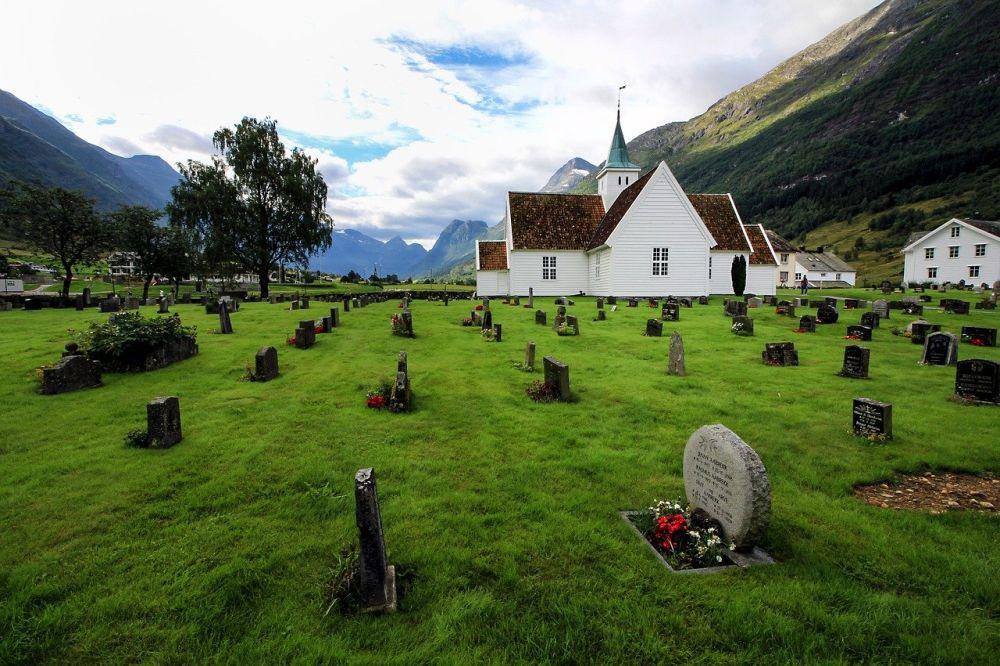 Gräber um eine Hozkirche herum in den Bergen. Die Holzkirche ist weiß gestrichen, die Gräber befinden sich auf einer Grünen wiese, und sind jeweils mit einem Stein gekennzeichnet. Vor einigen Steinen liegen ein paar Blumen. Das ebenerdiege Gelände ist umgeben von Bergen.