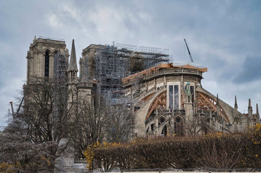 Der Notre Dame von hinten nach dem Brand. Das Dach fehlt, ein Kran hält teile eines Baugerüstes.
