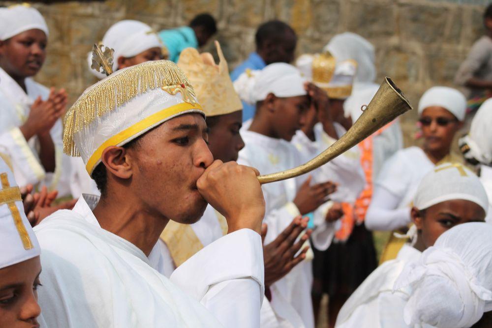 Ein Junge bläst in eine Tröte. Er hat ein Weises Religiöses Gewand an, mit einer Weissen Mütze, die einen glodenen Rand hat und ein glodenes Kruz auf der Stirn.