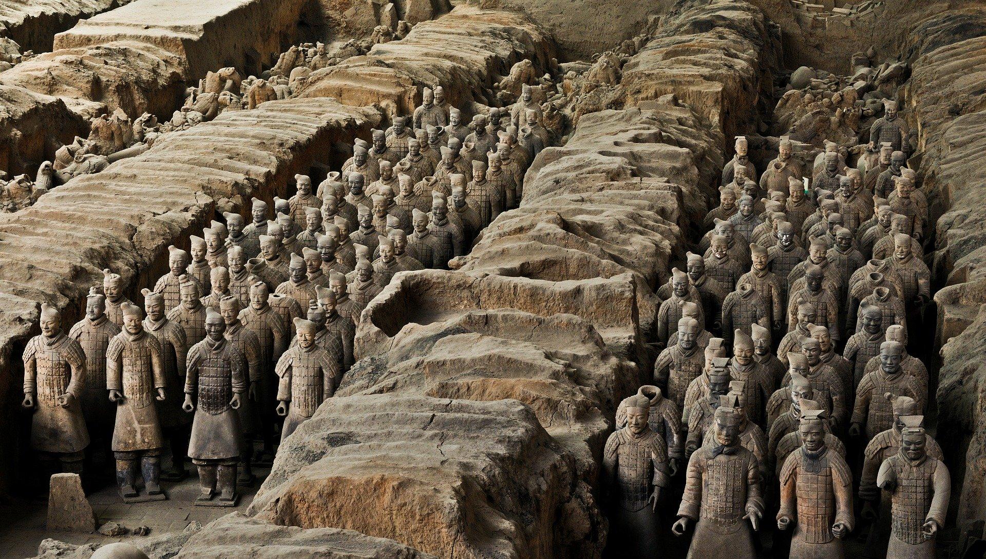Krieger der Terrakottaarmee stehen Aufgereiht in einem Grab. Es sind soviele, das das Ende nicht zu sehen ist.