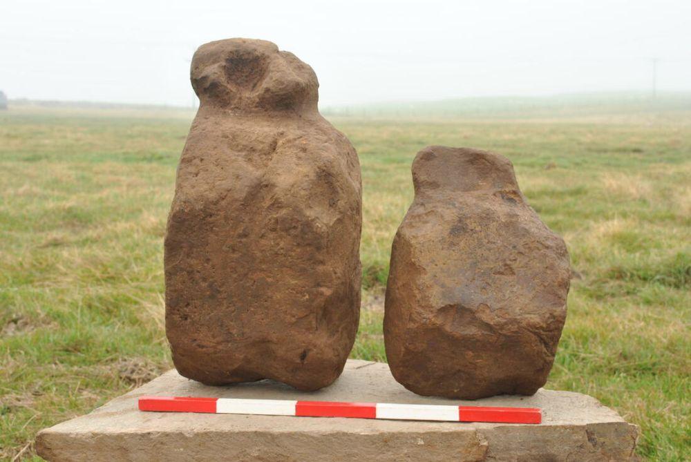 Zwei rotbraune Steine vor einer Wiese. Ein 50 dm Massstab ist vor sie gelegt. Die Steinfiguren aus den Orkney Islands sind von Menschenhand bearbeitet. Sie haben einen lang gezogenen klobigen unterbau, eine Art Hals und eine Art Kopf. Bei einer der Figuren ist der Kopf teilweise abgebrochen. Bei der anderen Figur befindet sich ein Loch an der Stelle des Gesichts.