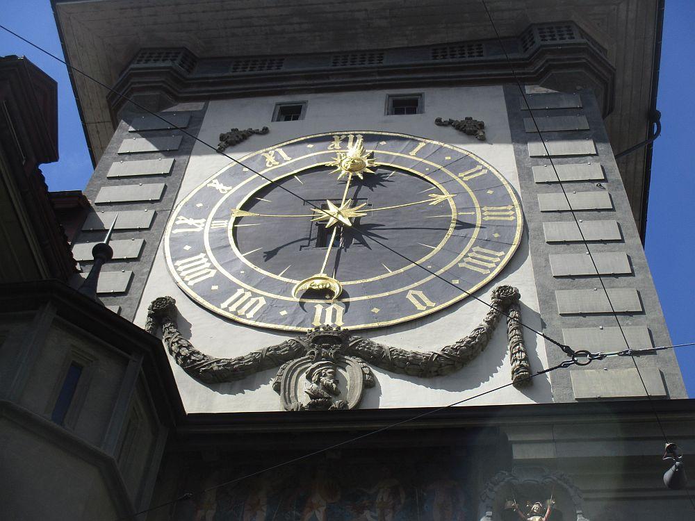 Eine Große Uhr mit einem schwarzen Ziffernblatt und Goldenen Lettern mit Lateinischen Zahlen. Es gibt drei Zeiger. Einen Für Minuten, einen Für Stunden, und einen der Mit an den Enden eine Sonne und einen Mond hat, und anzeigt ob Tag oder Nacht ist.