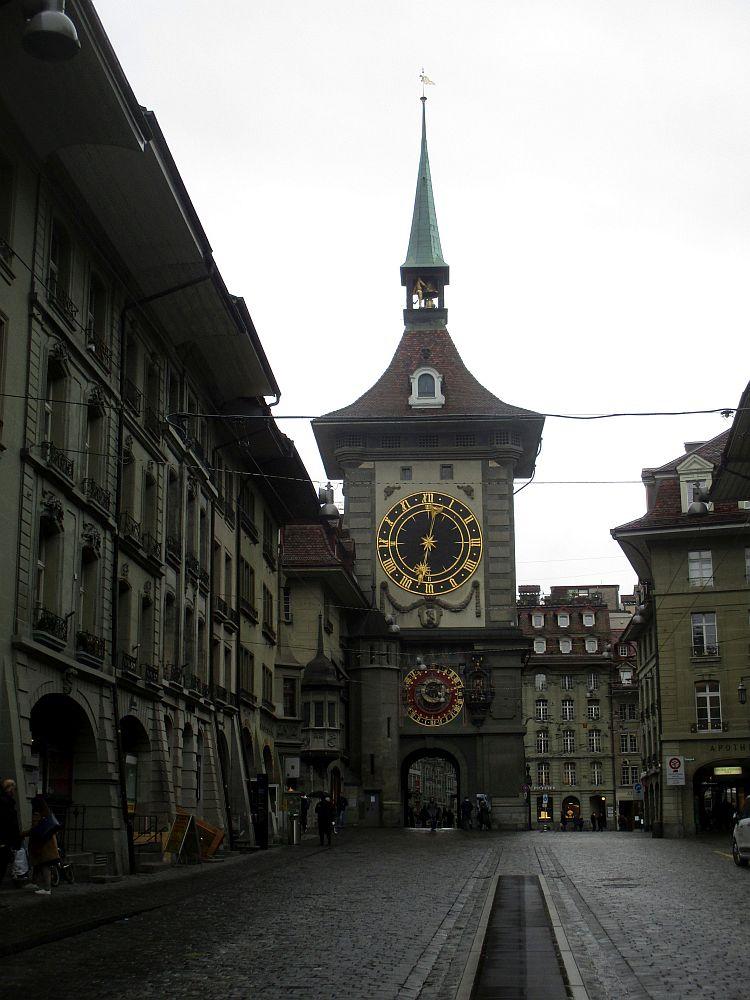 Die Berne Zytglogge aus der endfernung. Der Uhrenturm hat ein Schindeldach, das spitz zuläuft, Auf der Dachkrone befindet sich ein Uhrengeläut, das mit einer Kupferspitze geschützt wird. Der Turm steht in einer Strassenschlucht, in der sich links und rechts Arkadenhäuser erstrecken.