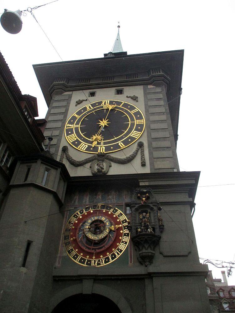 Der Turm der Zytglogge. Oben befindet sich ein grpßes Ziffernblatt eier Normal Fuktionierenden Uhr, und Untern das Astrolabium, das sehr Frabenfrph dargesteölt ist. Daben befinden sich einzenle Renaicanssefiguren, die sich mit einer Mechanik alle bewegen können.