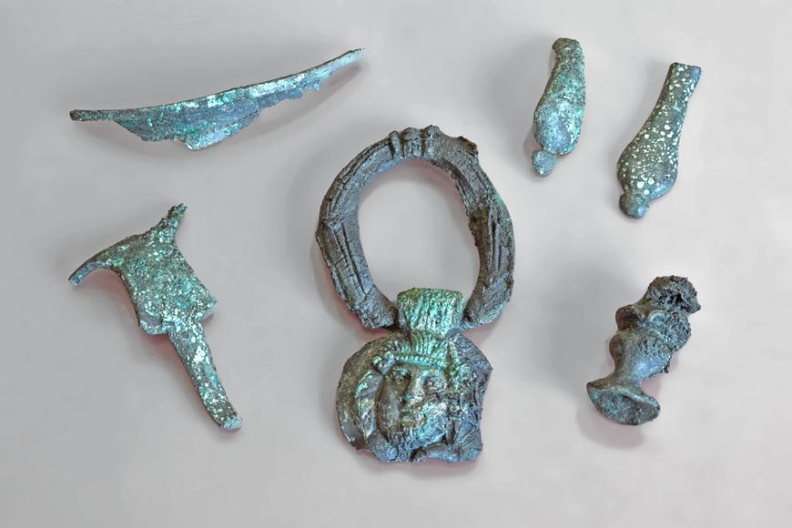 6 Bronzene Gegenstände. Bei den Meisen handelt es sich um Bruchstücke. In der Mitte ist ein Bonzering zu sehen, an dem eine Art Anhämger hängt. Der Anhäger ist filigran gearbeitet, und zeigt ein Gesicht mit Frsur. Es handelt sich um eine römische Maskendarstellung.