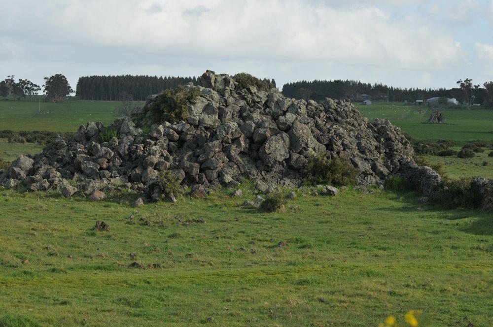 Ein Haufen grauer Steine auf einer Wiese.