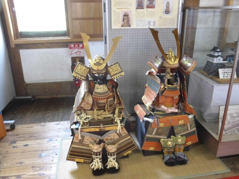 Zwei Samurai Uniformen, die eine ist braun mit Goldzierde, die andere Orange mit weniger zierelementen.