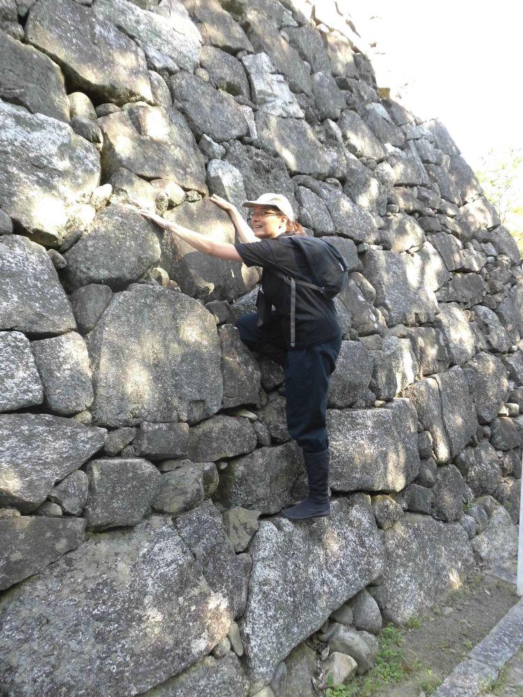 Eine Frau in schwarzer Kleidung mit einem Rucksack auf dem Rücken klettert an einer Mauer hoch.