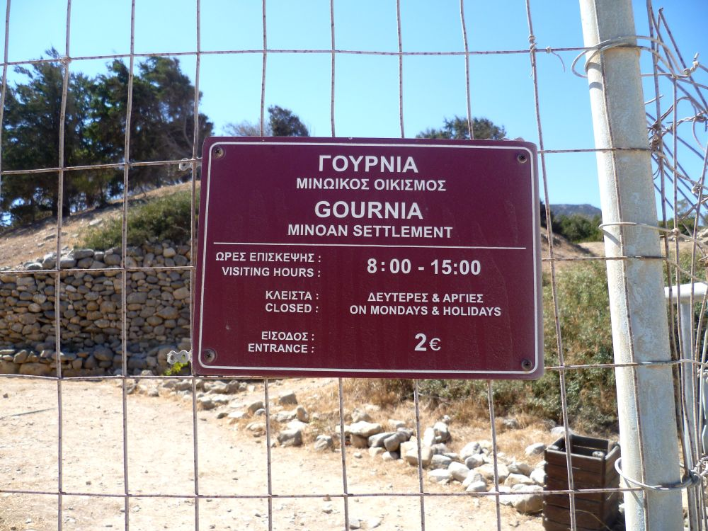 Ein rotes Schild in englisch und griechisch. Zu lesen ist: Gournia - Minoan Sttlemant. 8:00 - 15:00 Montags und Feiertags geschlossen, 2€ Eintritt.