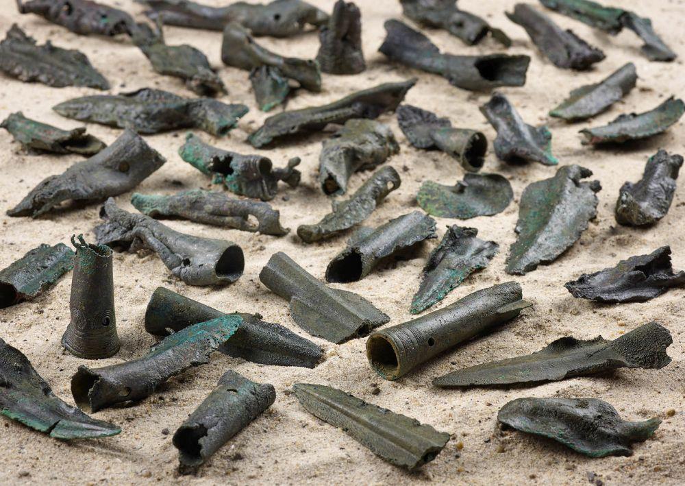 Viele Gegenstände liegen auf Sand. Es handelt sich um bronzene Lanzenspitzen. Sie sind alle etwas zerstört und haben schäden