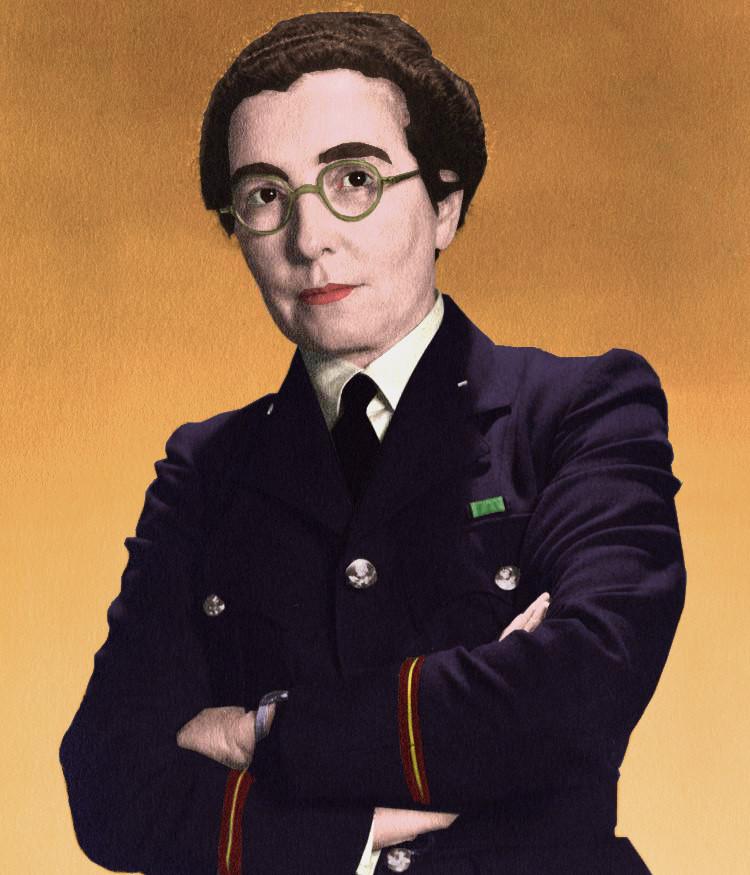 Eine Frau in einer US-Navy Militärjacke in Blau. Sie trägt ein weißes Hemd mit einer deutlich sichtbaren Krawatte unter der Jacke. Zudem hat sie eine Brille auf. Es ist eine weise Frau mit Braunen Haar. Ihr Name ist Harriet Ann Boyd Hawes.