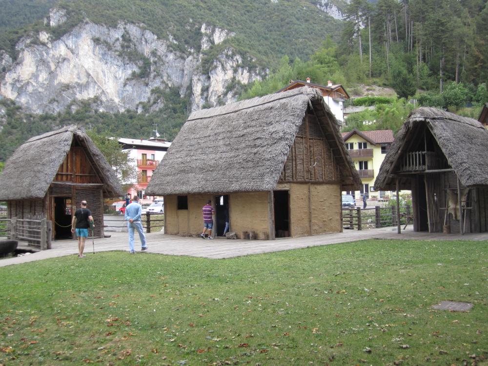 Grüne Wiese die in Holzbohlen übergeht. auf diesen holzbohnen sind Häuser Gebaut. Im Hintergrund sind die Alpen zu sehen.