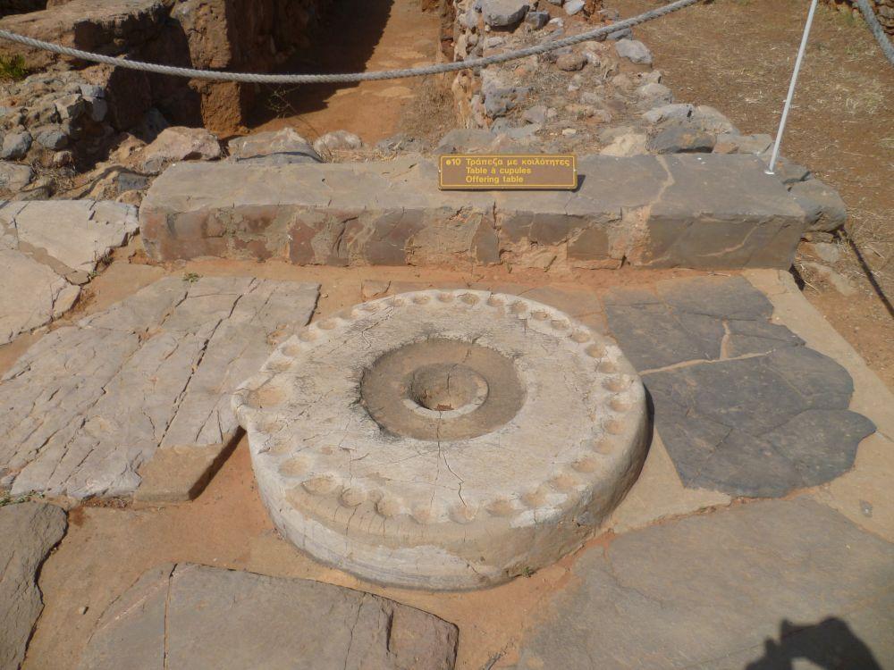 Ein Rundes Marmorobjekt, das auf dem Boden Liegt wie ein Kreis. Am Rand sind 33 gleich große Mulden angebracht, und eine sehr große Mulde.