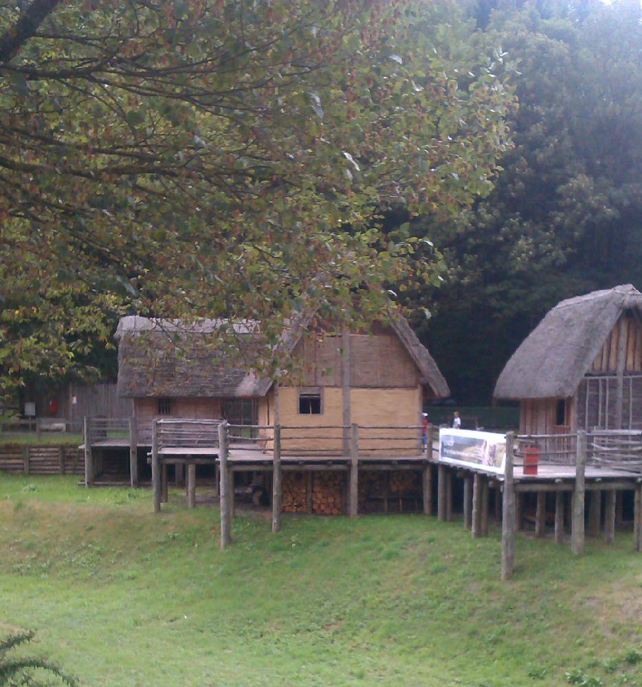 Die Hausrekonstuktionen Der Pfahlbauten am Ledrosee. Drei rekonstruierte Gebäude auf Holzplattformen am Uferrand. Diese Gebäude bestehen aus Holz, eines ist mit Lehm verputzt.