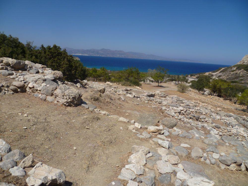 Im Vordergurng ruinen aus weissen Steinen. Im Hintergrund eine blaue Mittelmeerbucht.