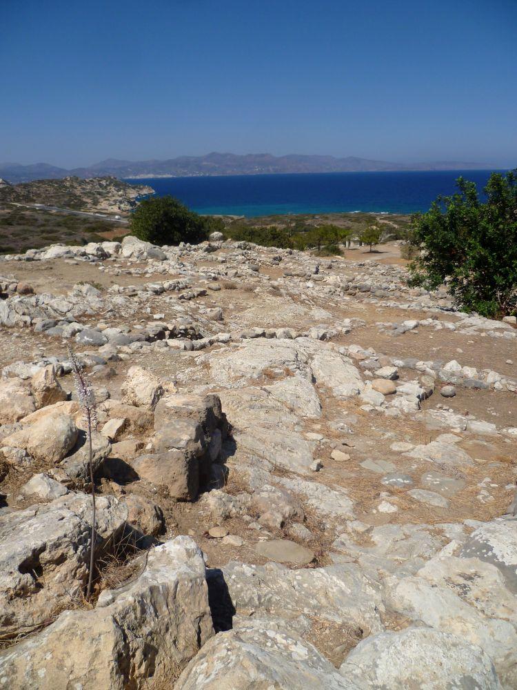 Im Vordergrund die Ruinen vin Gournia, im Hintergund lieg das Mittelmeer, beinde Orte sind nur getrennt durch einen dünnen Grünstreifen der mit Olivenbäumen bepflanzt ist.