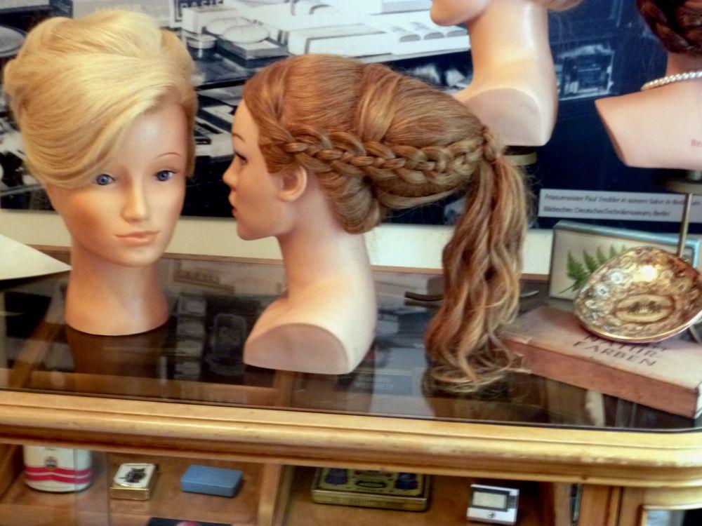 Zwei Schaufensterpuppenköpfe mit aufwendigen Perücken. Eine in Blond und eine in Braunhaarieg. Die Blonde Perücke ist von vorne zu sehen, die aufwendiege Flechtfrisur der Braunen Perücke ist von der Seite zu sehen.