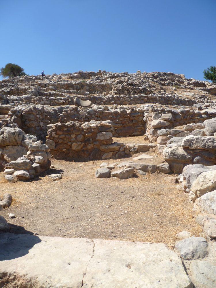 Ruinen. Grundmauern aus weissem bruchstein, die nur etwa einen Halben Meter Hoch sind. Sie verlaufen quer zu einem Hügel sodass man sehen kann, wie sich die Siedlung an einem Hügel orientiert.