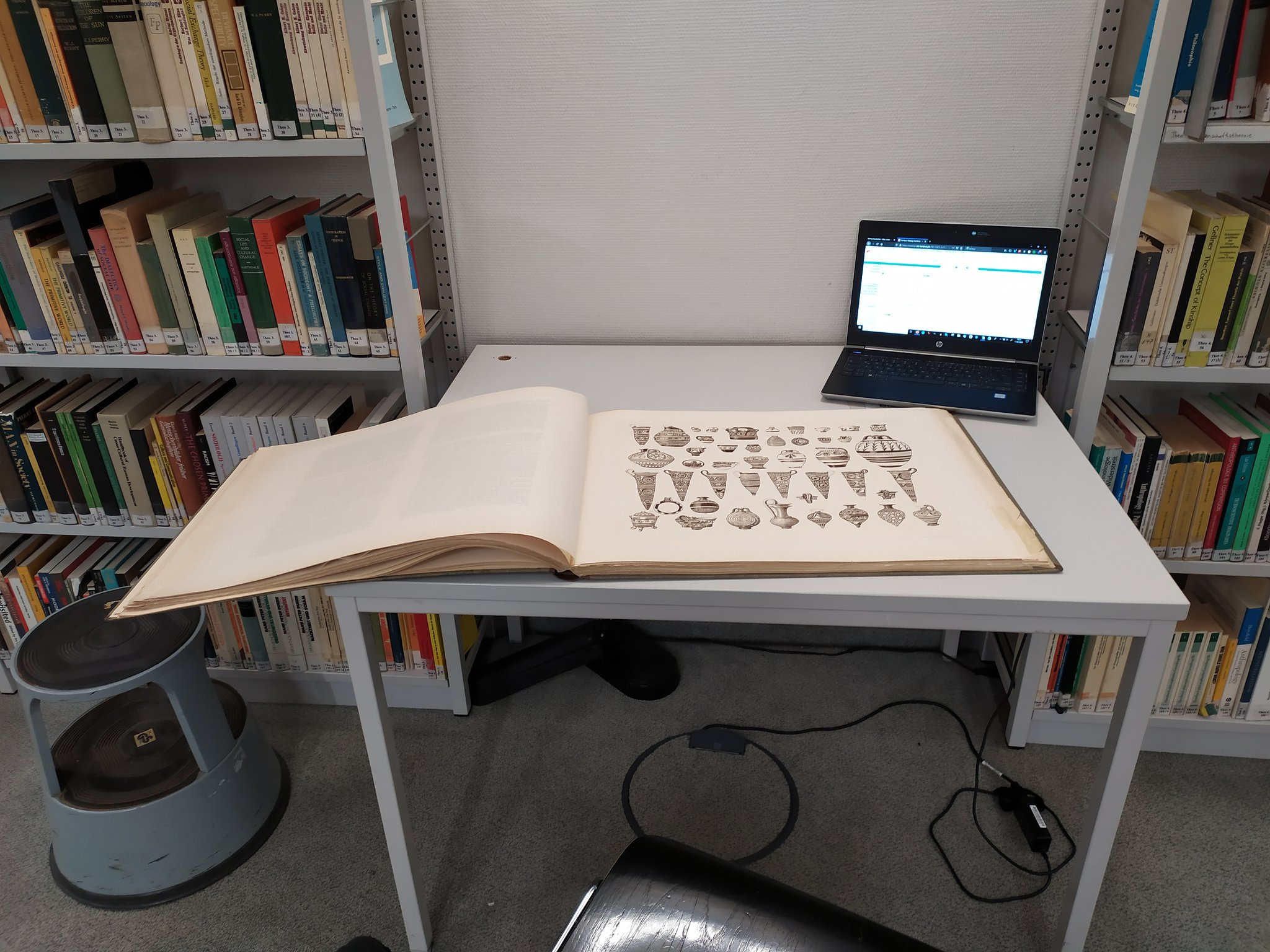 Ein Buch, dass viel größer ist, als ein Tisch, liegt auf einem Tisch, und hängt an einer Seite über. Im Hintergrund steht ein Laptop.