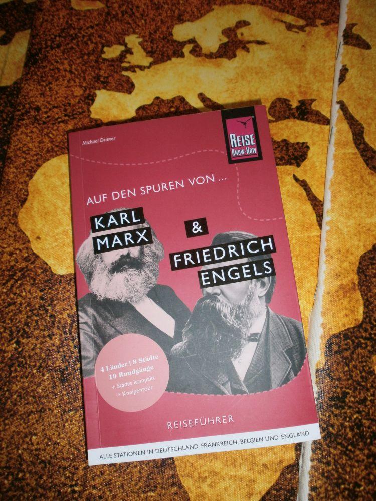 """Ein pinkes Buch liegt auf einer Weltkarte. Es handelt sich um """"Auf den Spuren von Karl Marx & Friedrich Engels"""" von Michael Driver,vom Reine Know how Verlag. Auf dem Bucheinband sind Marx und engels Collagenhaft in schwarz weis zu sehen, ihre Augen werden jeweils mit schwarzen Balken auf denen ihre Namen stehen verdeckt."""