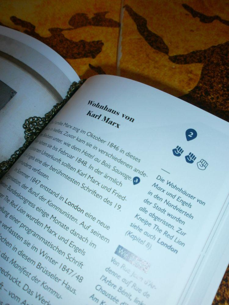"""Das Buch liegt auf einer Weltkarte und ist geöffnet. Zu sehen ist die Überschrift """"Wohnhaus von Karl Marx""""."""