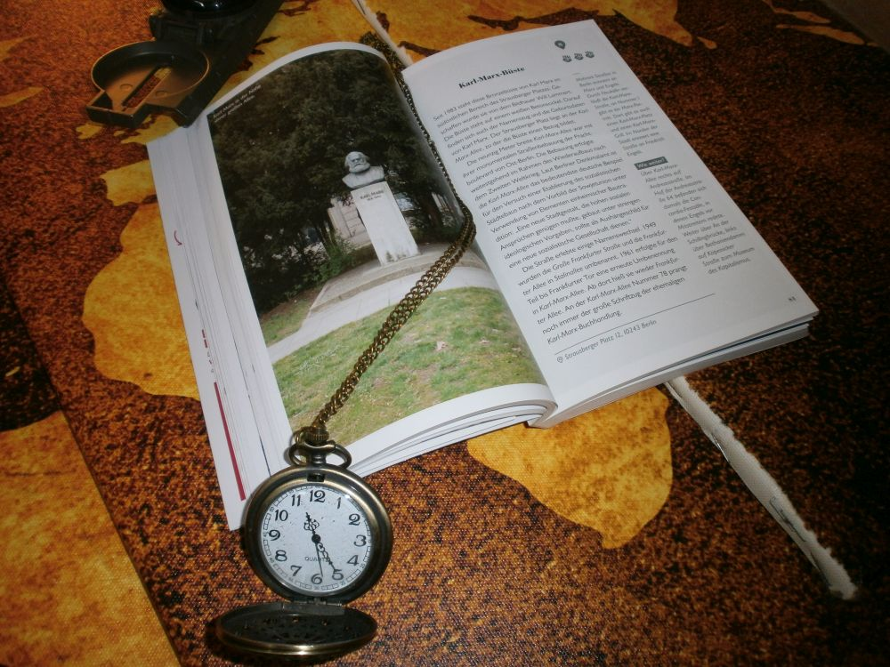 Das Buch liegt Aufgeklappt auf Weltkarten. Ein großes Bild mit einer Marxbüste auf einer Wiese ist zu sehen.