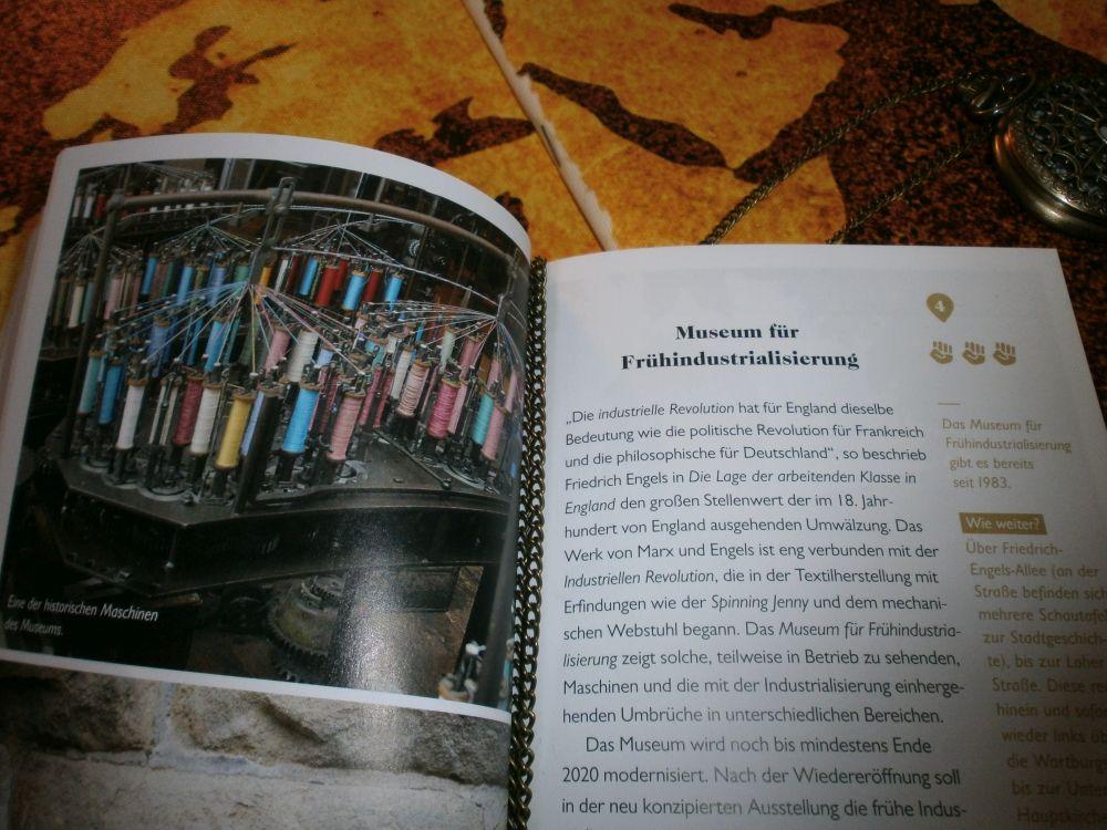 """Das Buch ist aufgeklappt. Auf der linken Seite ist ein großes Bild mit Garnrollen die in eine Maschiene eingesannt sind, auf der anderen Seite ist die Erklärung abgebildet und die Kapitelüberschrift. Sie heißt: """"Museum für Frühindustrialisierung"""""""