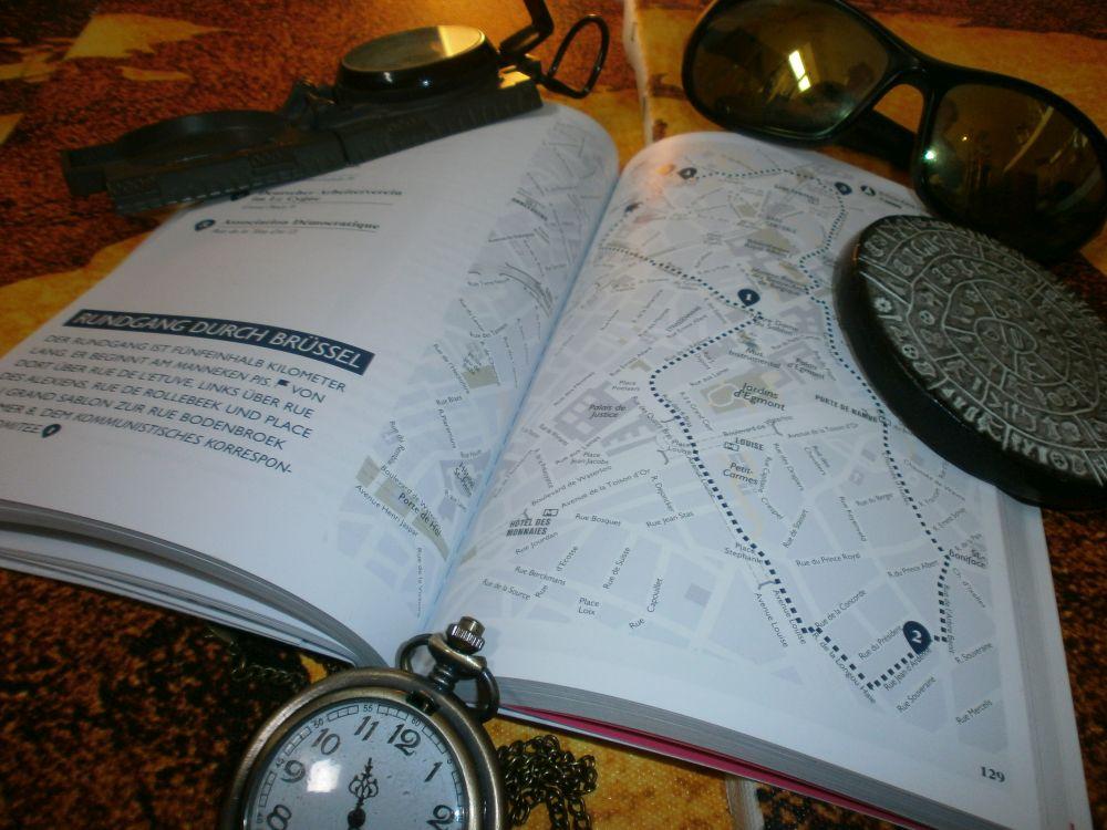 """Das Buch liegt geöffnet auf Weltkarten. Zu lesen ist """"Rundgang durch Brüssel"""" eine Karte von Brüssel mit einer eingezeichneten Route ist dargestellt."""