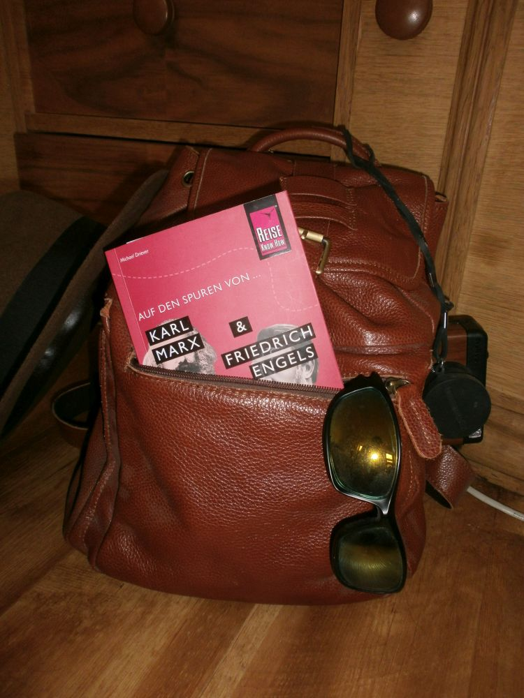 Ein Lederrucksack der für eine Reise ausgestattet zu sein scheint. Eine Sonnenbrille schaut aut aus ihm heraus, und ein Fotoapperat. Ausserdem ist ein Hut an den Rucksack gelaht. Das Buch Auf den Spuren von Karl Marx 6 Friedrich Engels schaut aus dem Rucksack heraus.