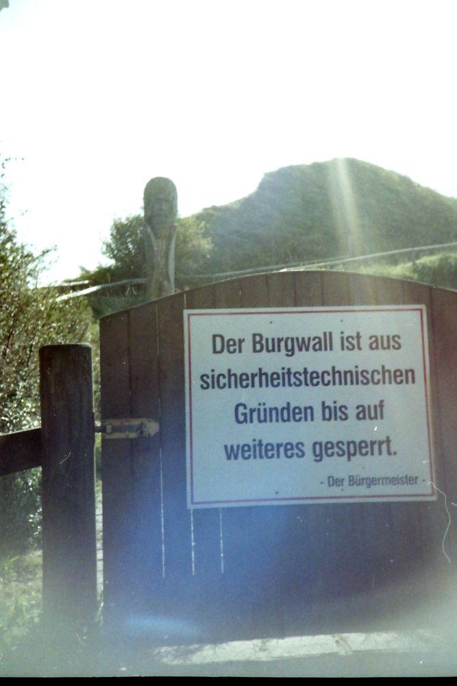"""Ein Tor mit einem Schild auf dem Steht: """"Der Burgwall ist aus sicherheitstechnischen Gründen bis auf weiteres gesperrt. - Der Bürgermeister-"""