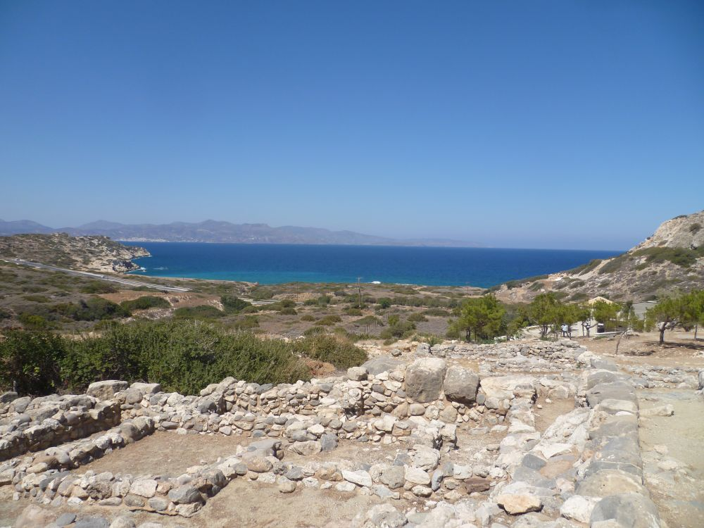Im Hintergrund befindet sich eine Blaue Mittelmeerbucht, im Vordergrund ragen steinernde Ruinen aus dem Boden
