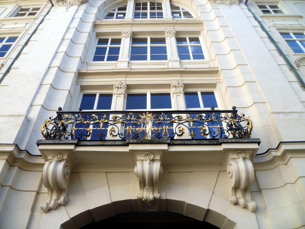 Die Innsbrucker Hofburg, Ein Balkon der mit solg verziehrt ist vor einem Weis verputzten Barockbau mit hohen Fenstern.