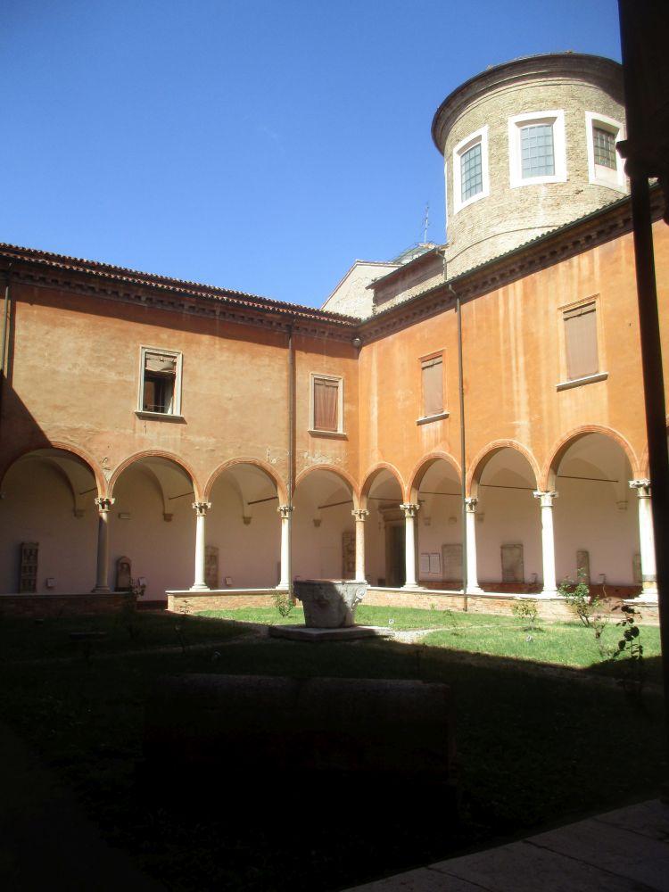 Der Innenhof eines mediteranen gebäudes. Es gibt einen Laubengang, der aus einem Bogengang besteht der auf Romanische säulen gestützt ist. Im Inenhof ist eine Wiese, und das Gebäude seöber ist Orange.