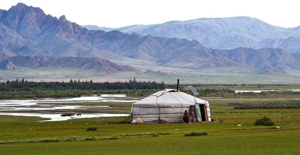 Eine Yurte in einer grünen Graslandschaft. Im Hintergrund stehen Die Berge des Himalaya.