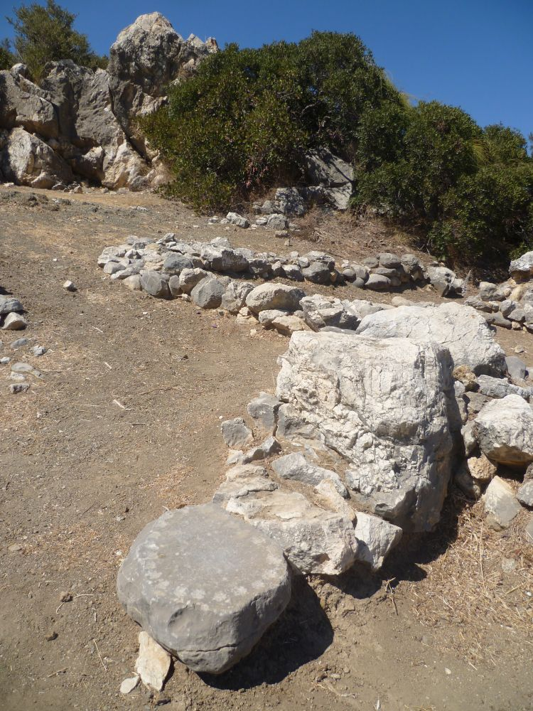 Teile von Ruienen aus Stein ragen aus dem Boden. Im Vordergrund befindet sich ein Grauer Stein, der Rund ist, auf dem Boden liegt und am rand eingetiefte mulden hat die kreisrum angordnet sind.