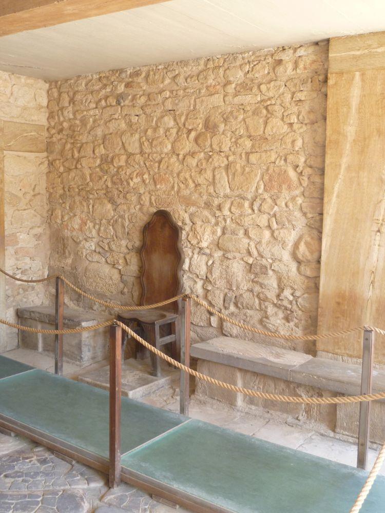 Eine Steinwand, mit steinbänken. Diese sind unterbrochen, dort steht ein Holzstuhl, der den Alabasterthron von Knossos darstellen soll.