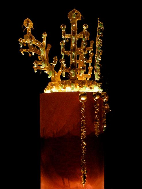 Eine Goldkrone mit Jadeanhängern. Die Krone besteht aus einem Kopfring. Und 4 nach oben ragenden ausläufern, die Baumstämme darstellen sollen. Ausserdem hängen einige Goldketten von dem Kopfring herab.